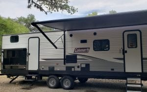 Exterior view of a rental RV showing door, and 2 canopies out