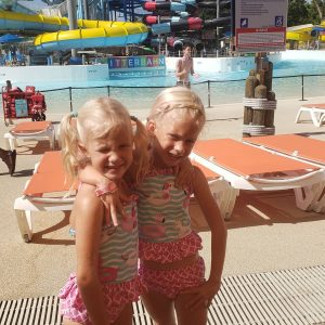 Two little girls in bathing suits hugging